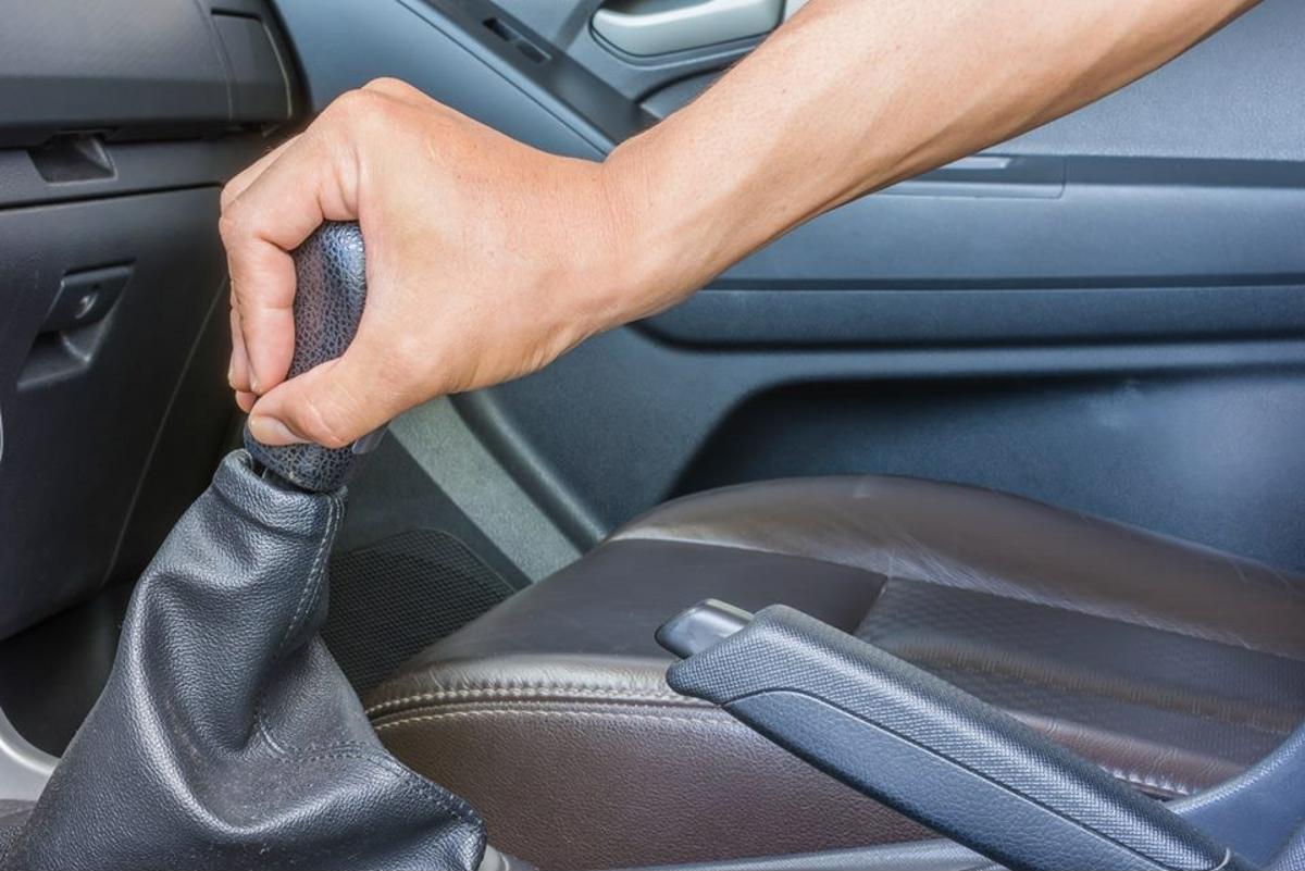 motorista com a mão no câmbio de marchas do carro