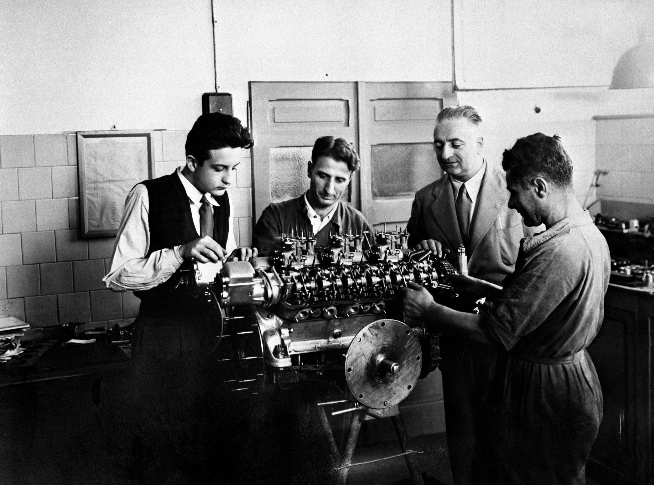 Alfredo, à esquerda, observa a montagem de um motor com o pai, na foto, entre dois funcionários (Ferrari/Divulgação)