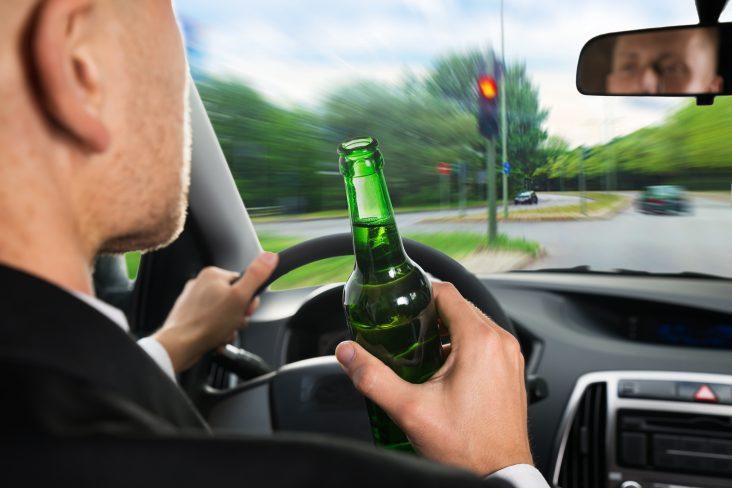 Motorista com garrafa de cerveja na mão bebendo ao dirigir