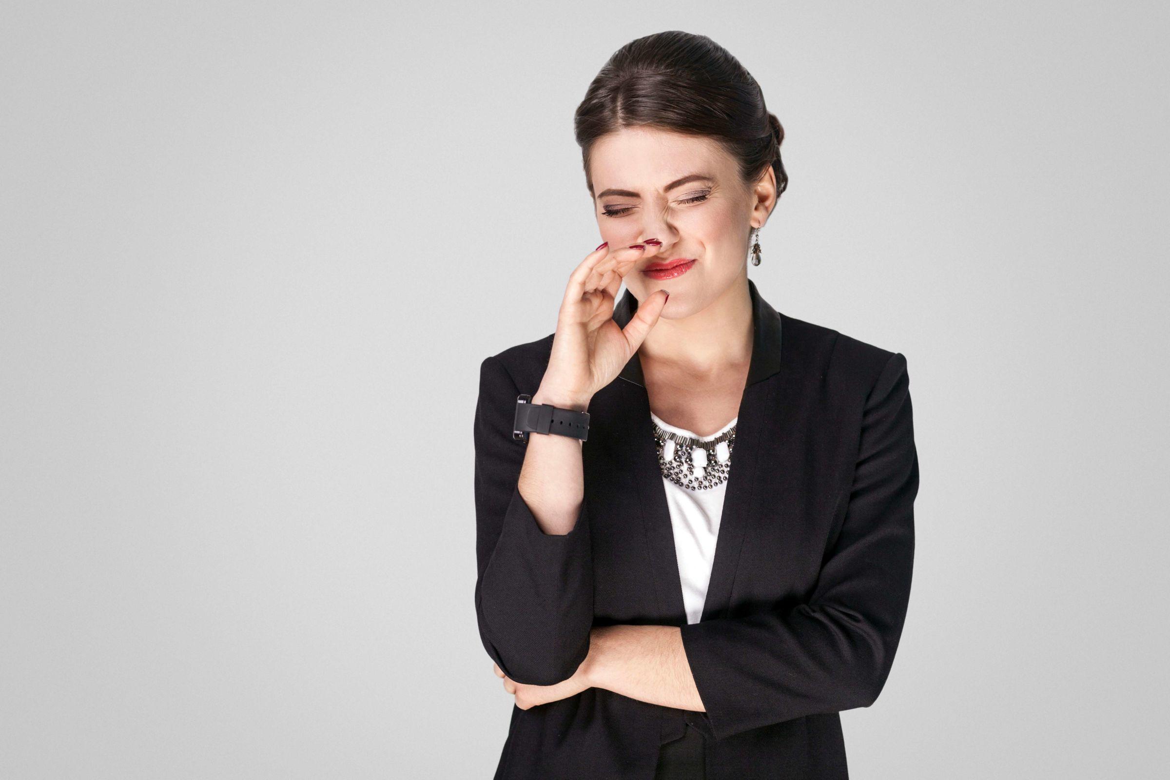 mulher torce o nariz em reação a fedor como eliminar mau cheiro no carro