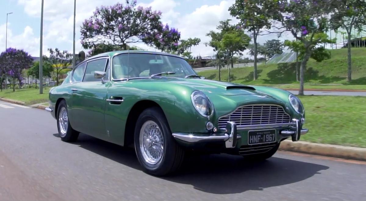 Aston Martin DB6 1967 verde rodando próximo a praça