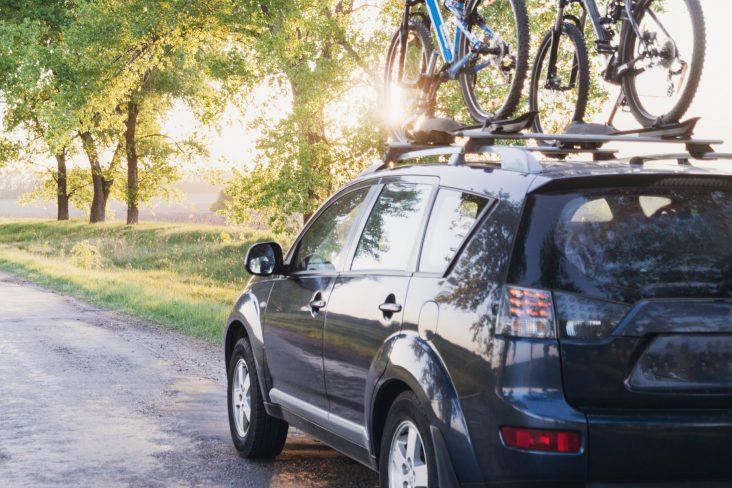 Mitsubishi Outlander cinza transportando duas bicicletas no suporte de teto
