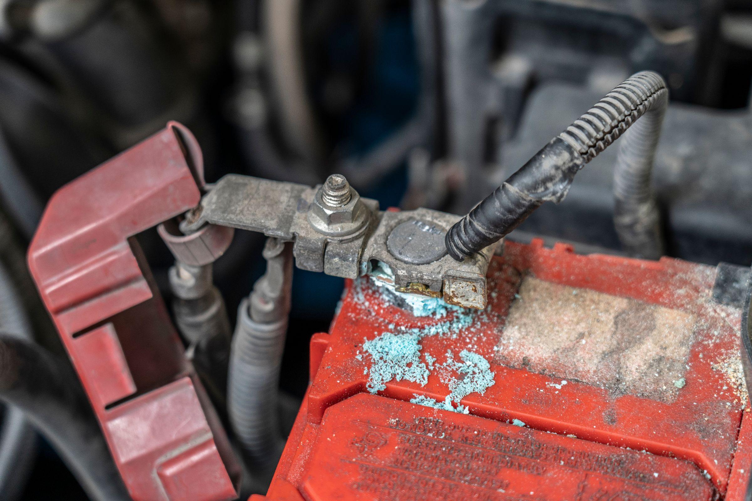 bateria de carro vermelha mostra acumulo de oxidacao zinabre ao redor do terminal
