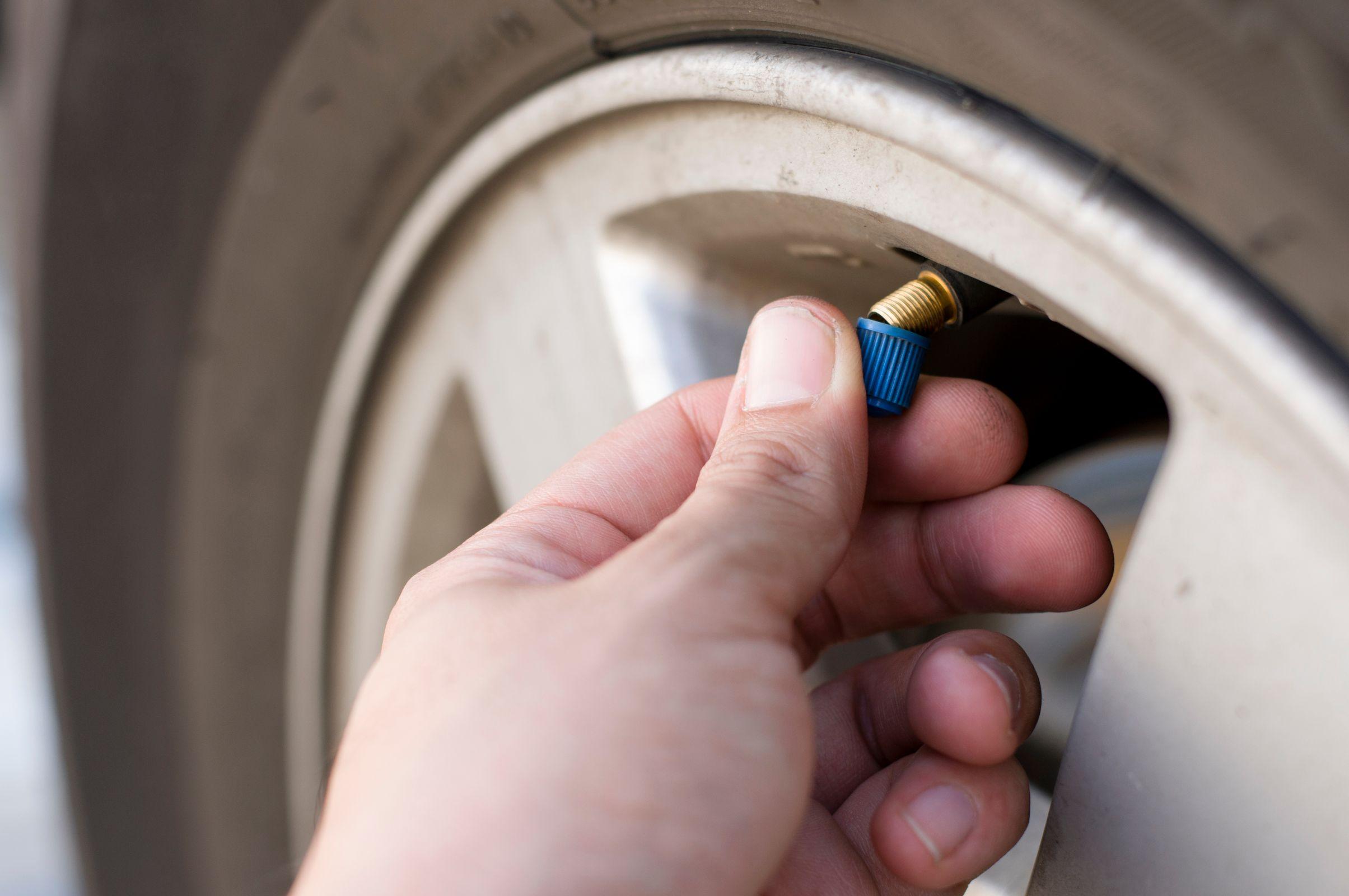 Pessoa abrindo a tampa da válvula do pneu do carro