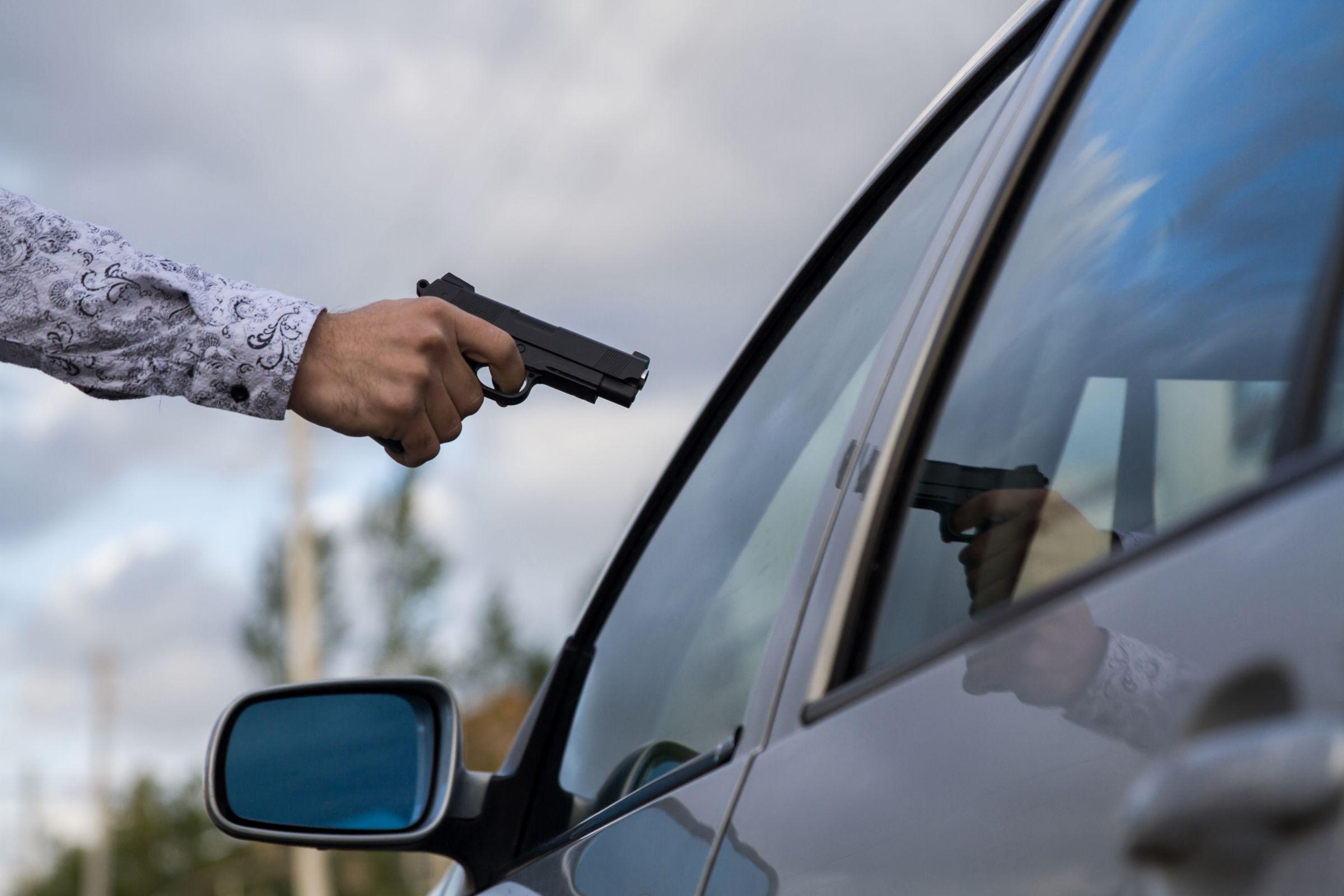 mão masculina apontando arma de fogo para vidro de carro blindado