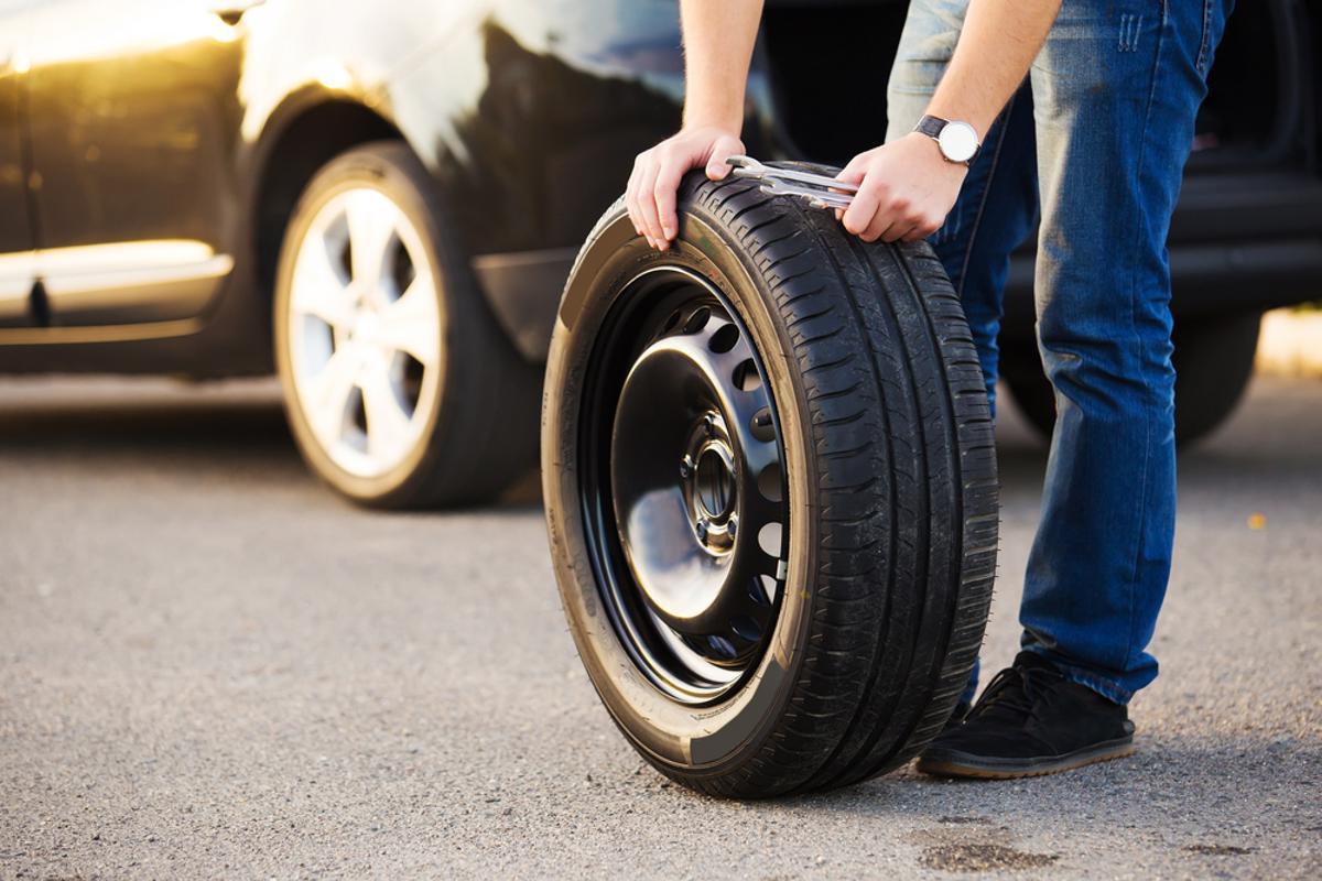 homem com pneu estepe sobressalente nas mãos em frente a veículo parado