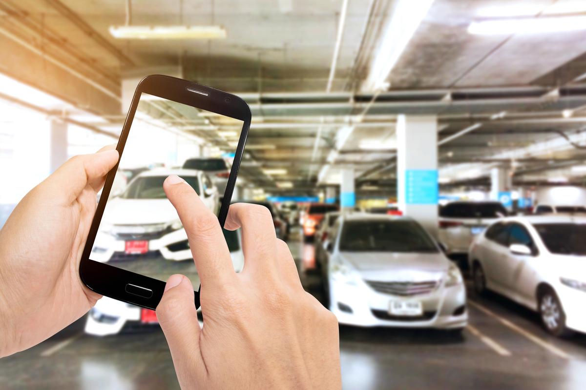 Pessoa com celular na mão fotografando seu automóvel para vendê-lo na internet