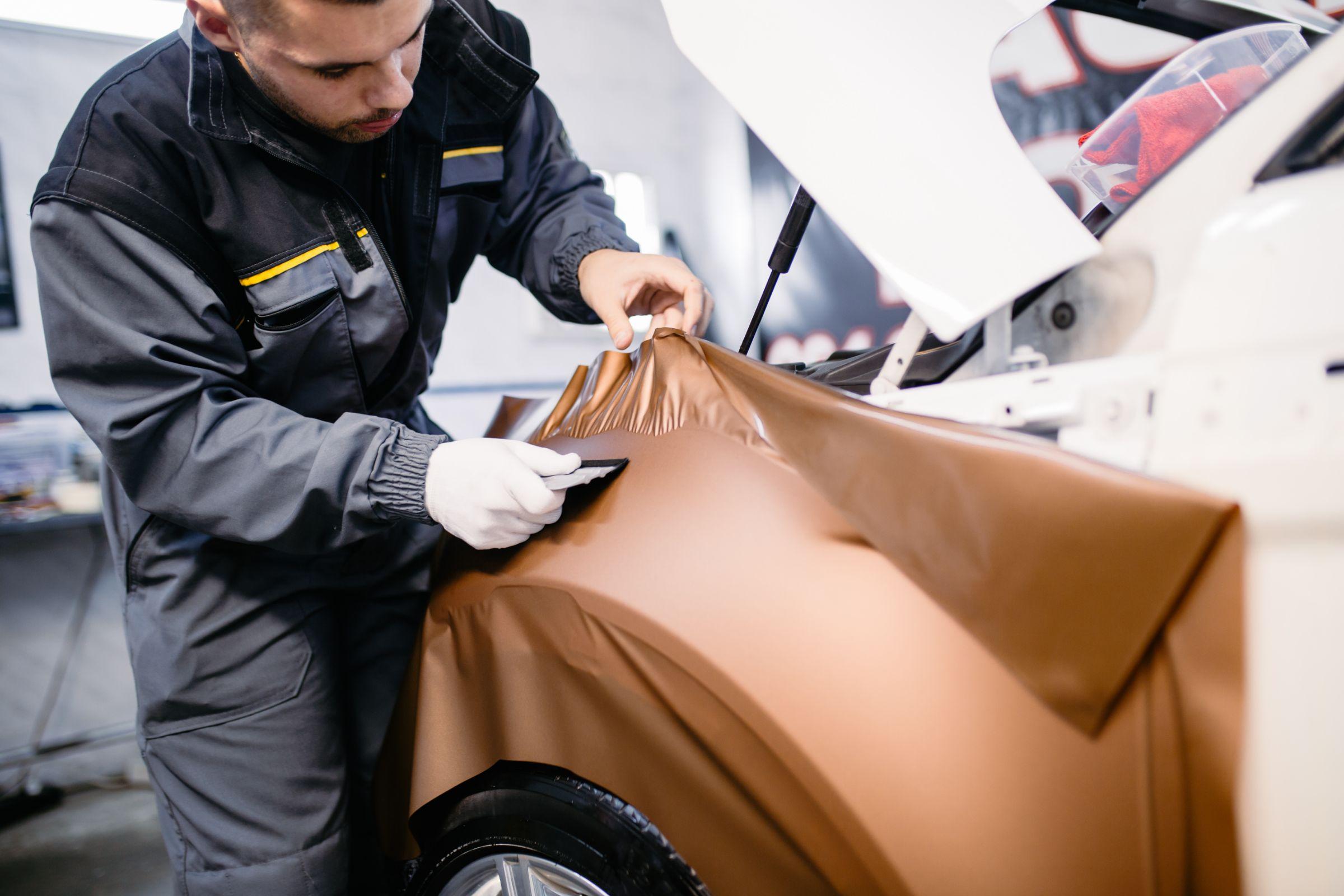 homem envelopa carro branco com adesivo dourado
