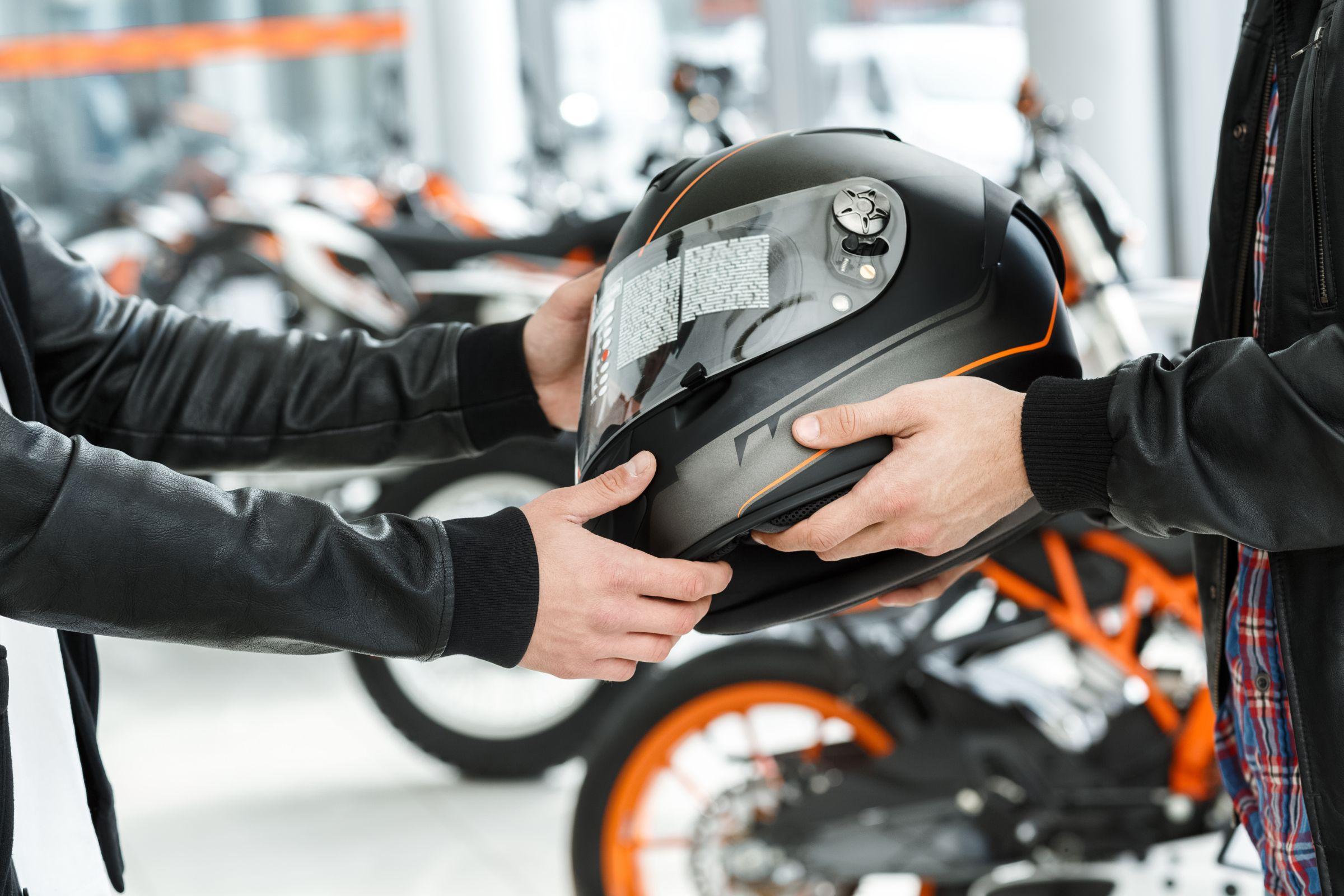 vendedor entrega capacete preto a motociclista
