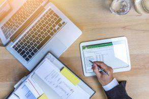 mão masculina mexe em ipad ao lado de computador e caderno de recibos representando dados para declarar carro no imposto de renda