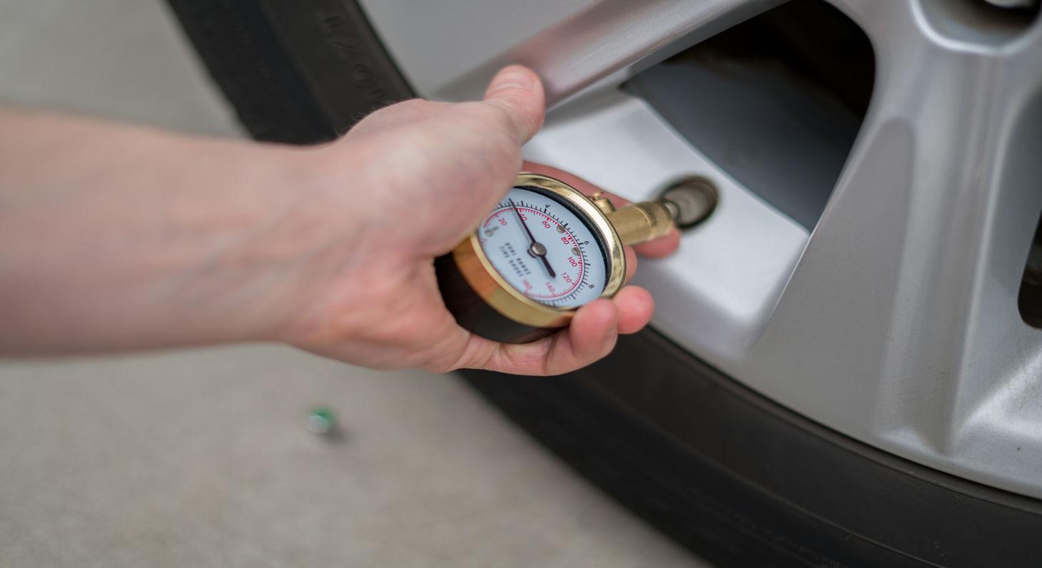 Pessoa conferindo a pressão dos pneus do carro