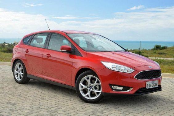 Ford focus hatch vermelho estacionado em frente ao mar