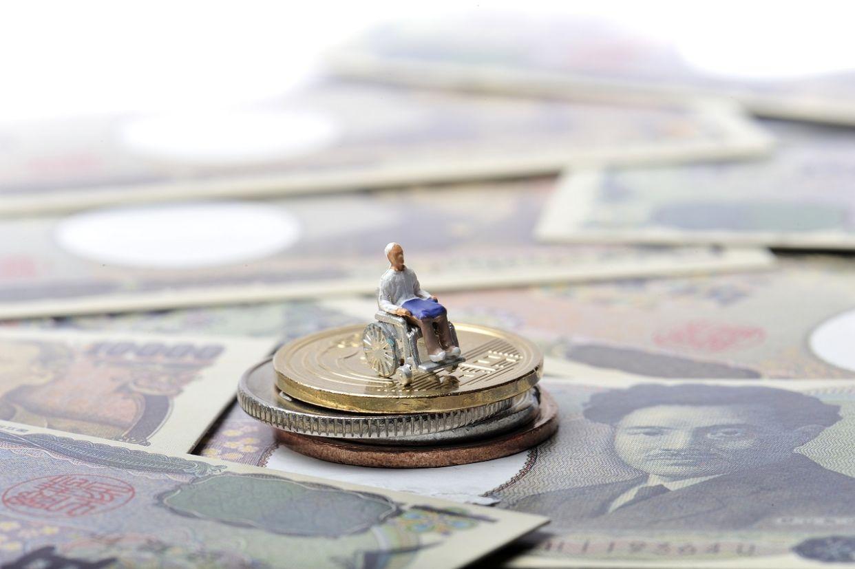 cadeirante de brinquedo em cima de moedas e notas