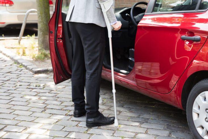 homem de muleta entrando em carro vermelho