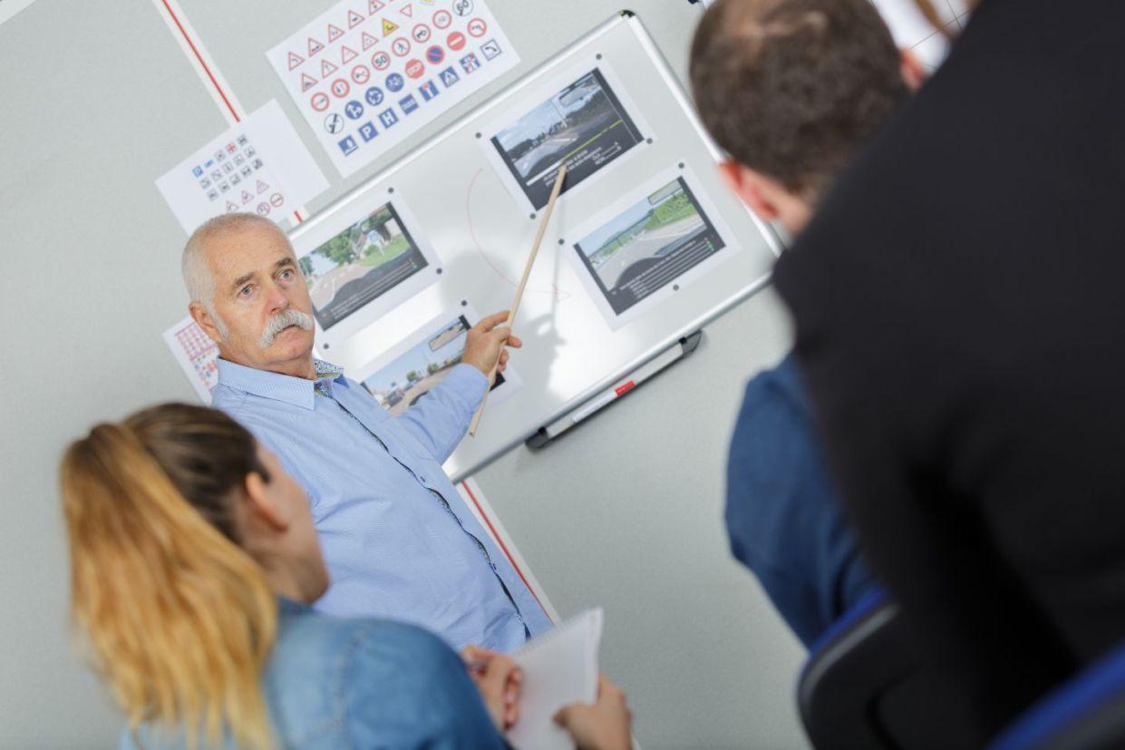 Instrutor indica imagens em aula para três motoristas em autoescola