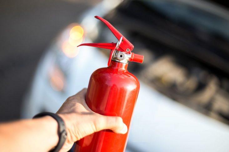extintor de incêndio em frente ao capô de carro aberto