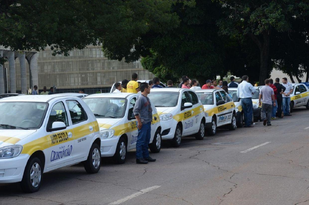 fila de carros de autoescola brancos em rua brasileira