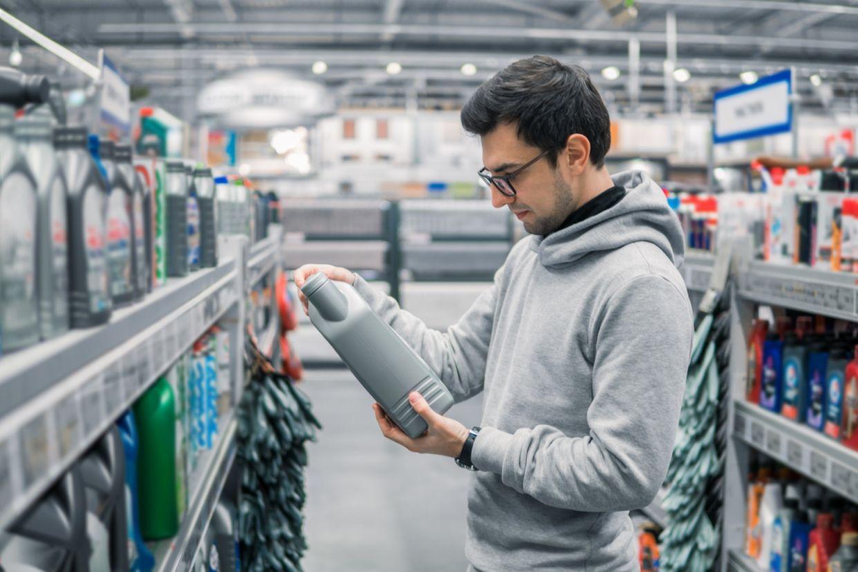 homem le o rotulo de um frasco de oleo lubrificante em frente a uma prateleira com diferentes tipos de oleo