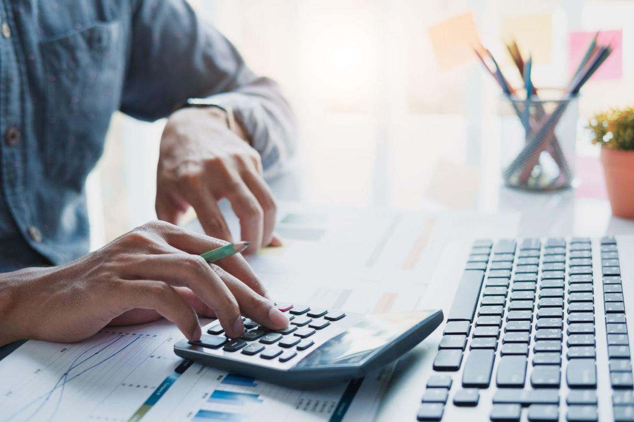 homem com lápis na mão usando calculadora representando calculo do ipva a vista ou parcelado