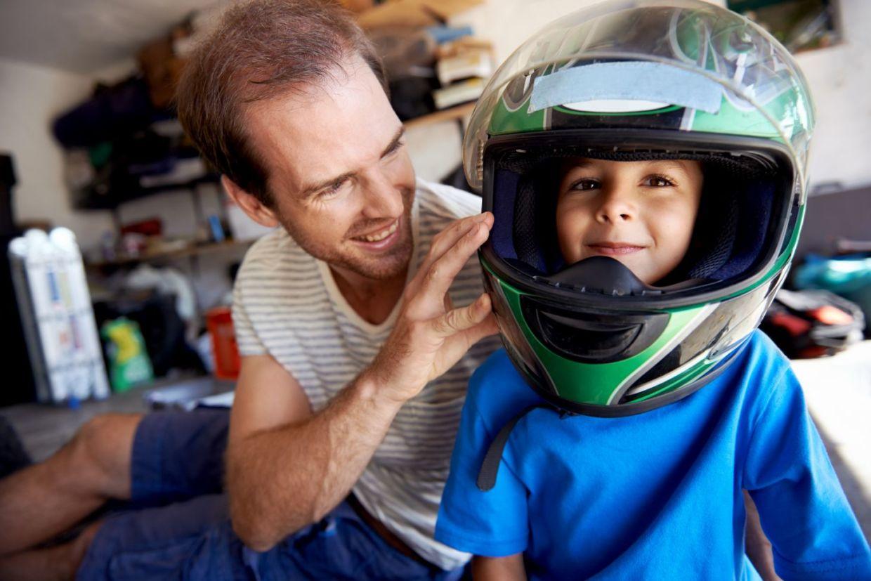 Adulto coloca capacete em crianca