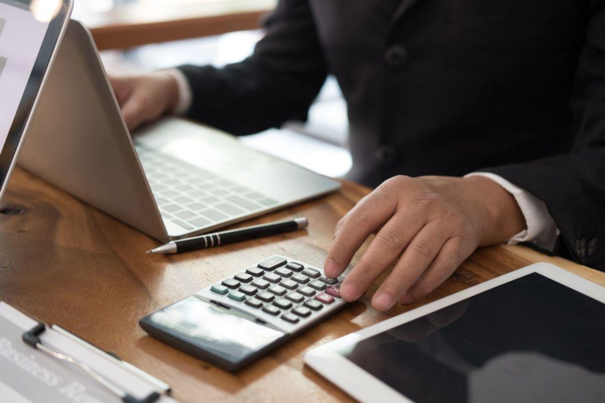 Mão masculina calculando e registrando informações no computador