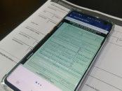celular com documento do carro digital aberto sobre crlv impresso