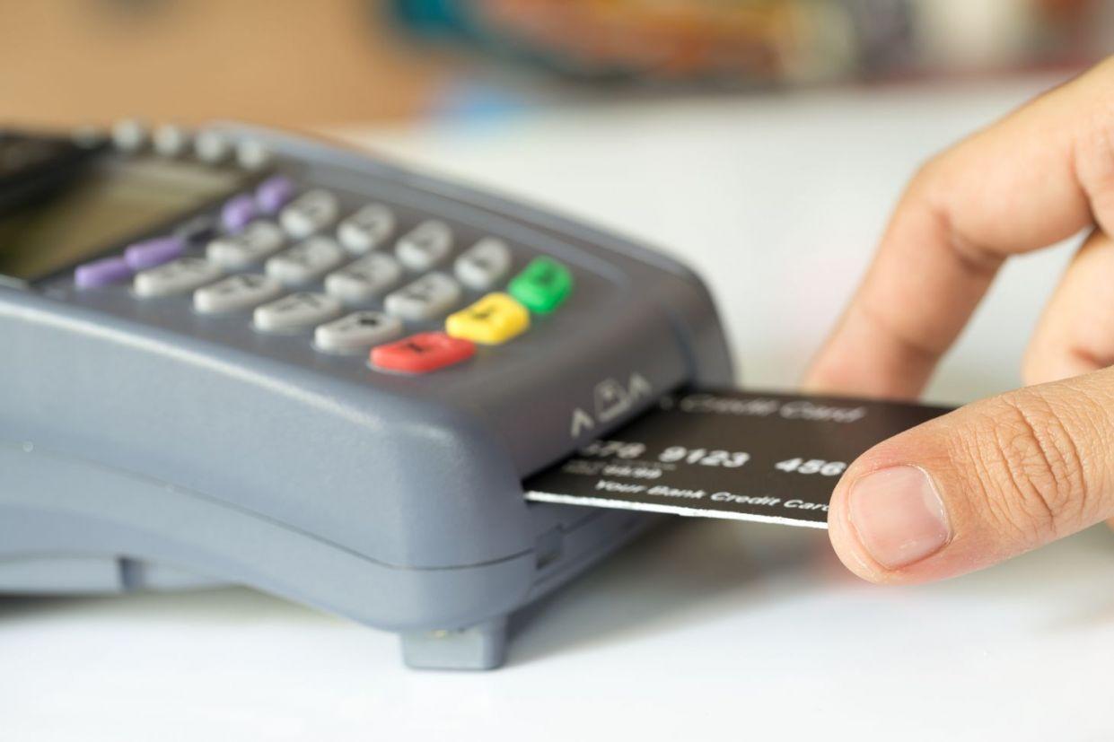 mão humana insere cartão preto em máquina