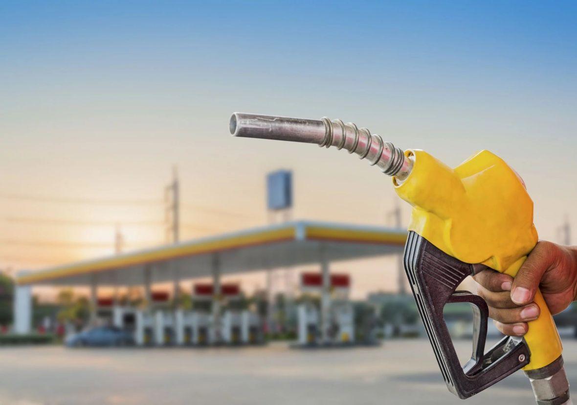 Mangueira de abastecimento da nova gasolina brasileira com o posto de combustível ao fundo