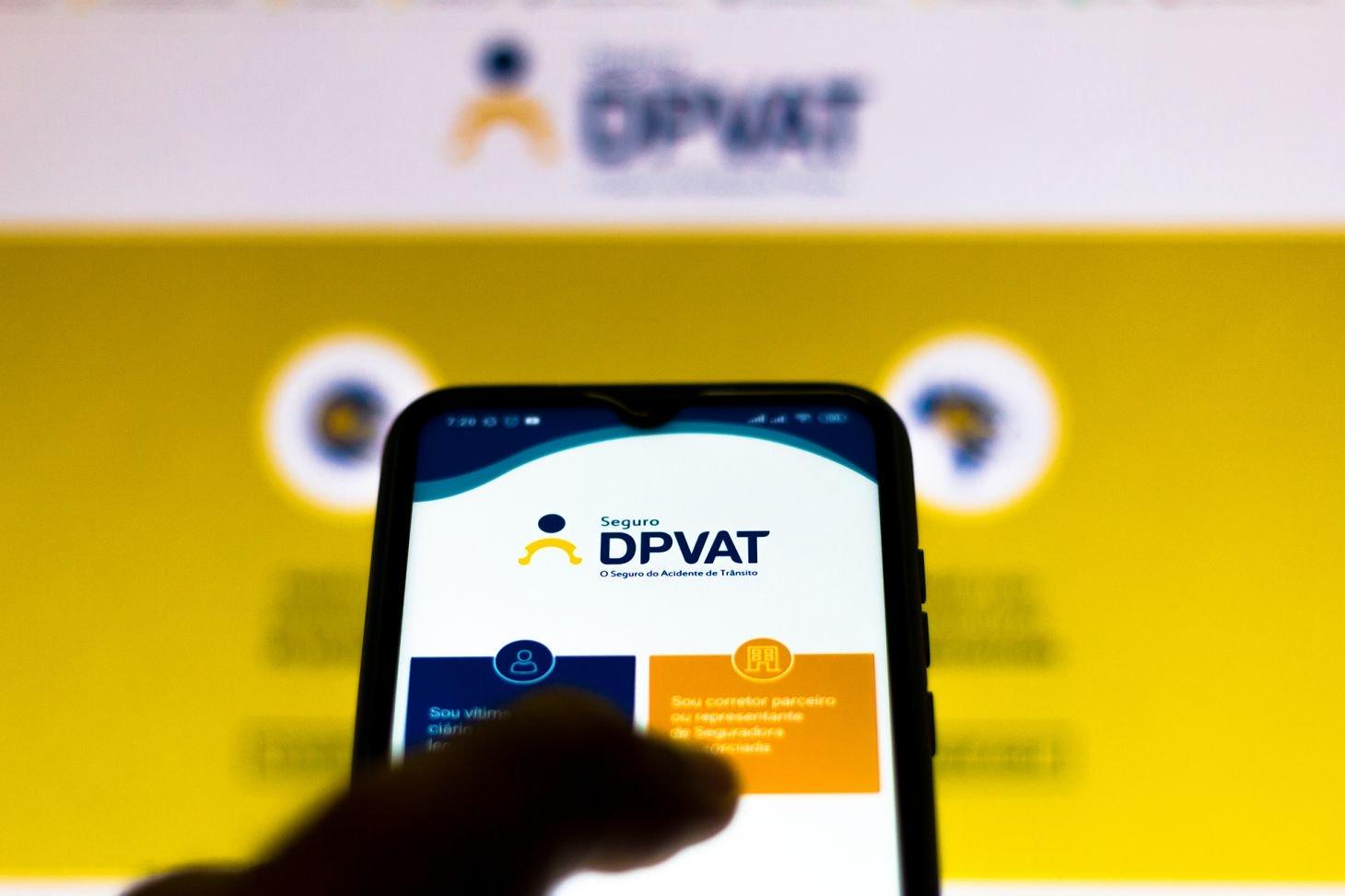 imagem em celular mostra aplicativo do seguro dpvat para celular com imagem do site no fundo