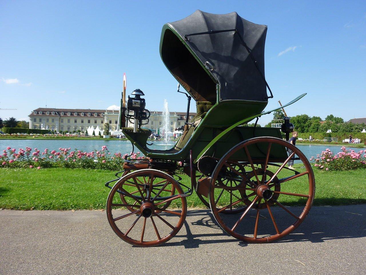 1888 flocken elektrowagen tido como o primeiro carro eletrico do mundo e exposto em uma pista com plantas e flores ao fundo