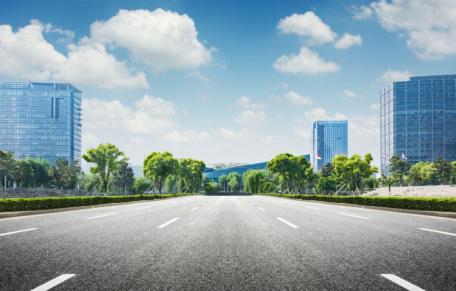 imagem mostra uma rua pavimentada sem pessoas e sem carros com predios ao redor e o ceu azul acima