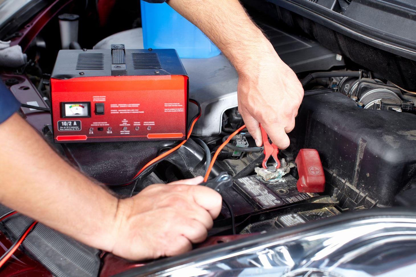 pessoa conecta cabos de um carregador portatil nos terminais da bateria no motor de um carro
