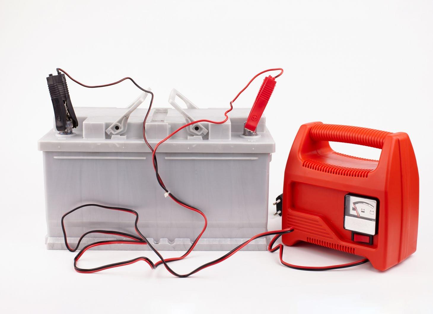 carregador de bateria de carro vermelho com cabos conectados a uma bateria sobre fundo branco