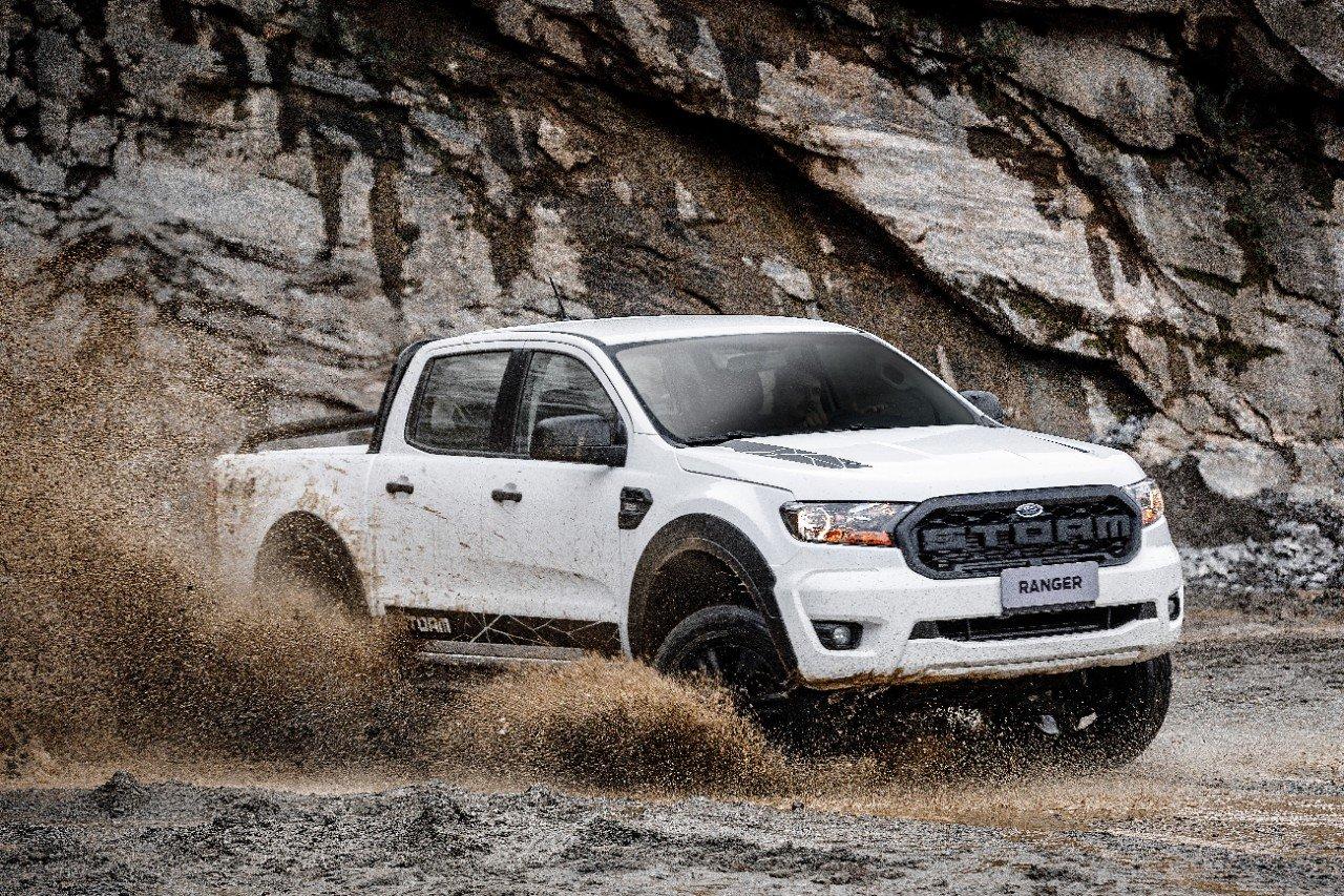 ford ranger 2020 storm na cor branca em uma estrada de terra vista pela dianteira em tres quartos com uma montanha ao fundo