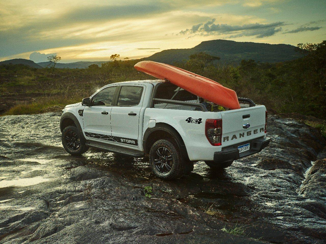 ford ranger 2020 storm na cor branca vista pela traseira tres quartos com um caicaque na cacamba sobre uma montanha