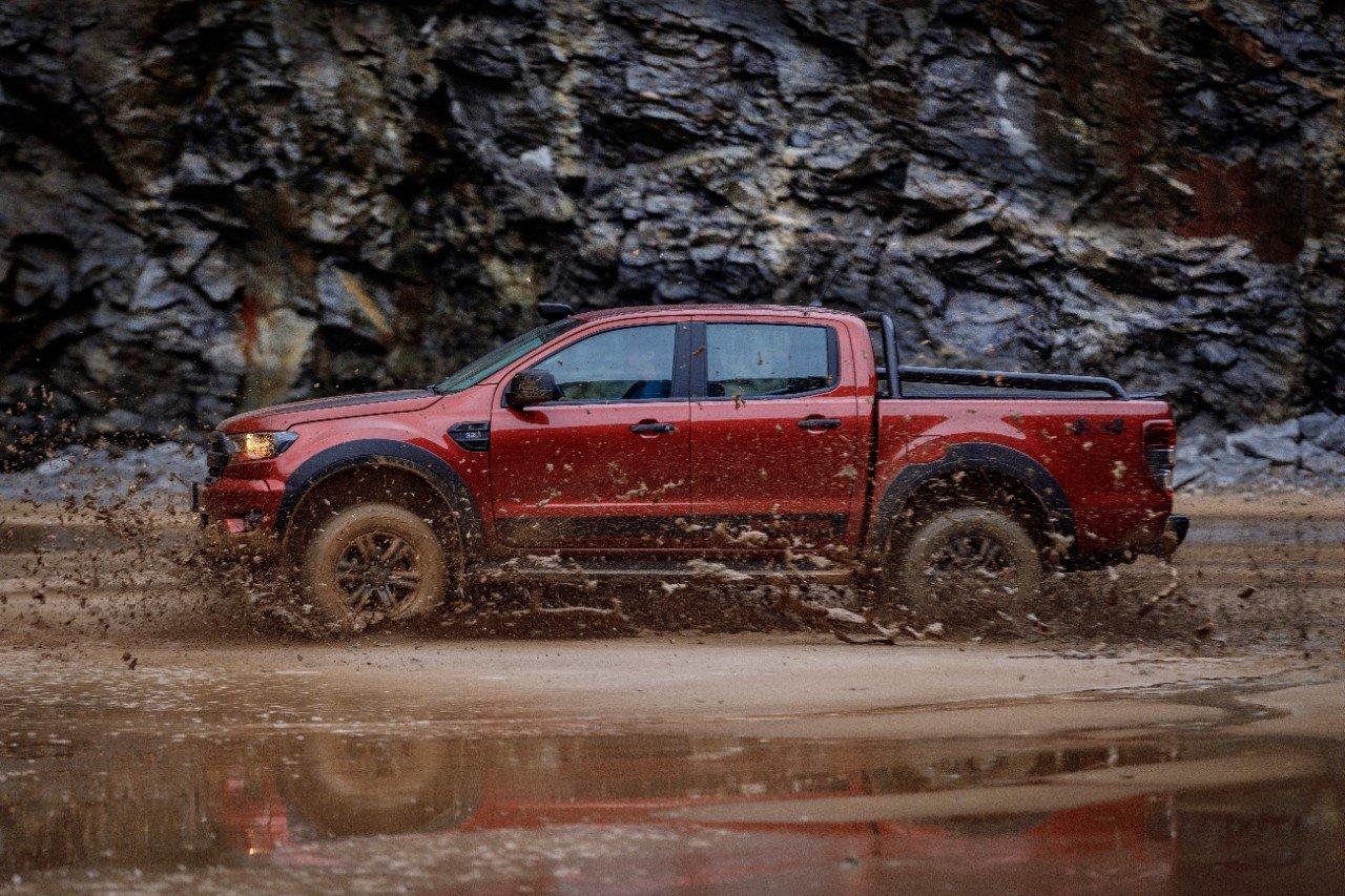 ford ranger 2020 storm na cor vermelha vista pela lateral andando na lama com rochas ao fundo