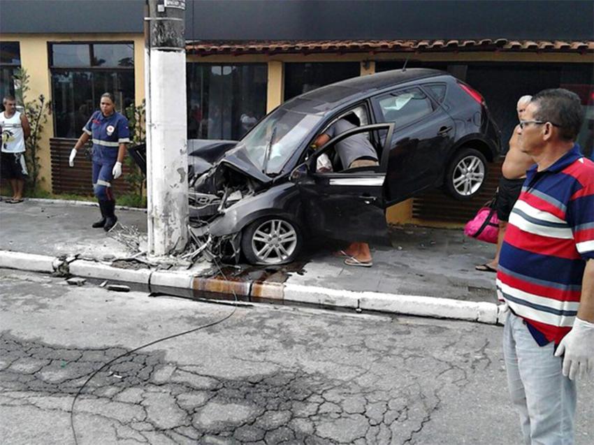 acidente transeuntes olham hyundai i30 preto batido no poste em rua do guaruja foto corpo de bombeiros