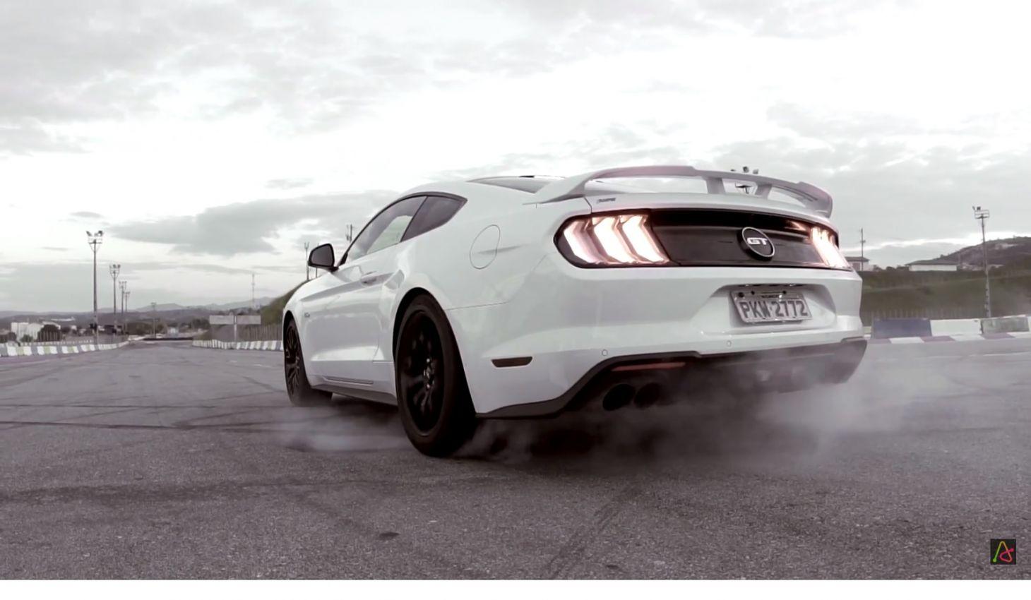 Ford Mustang GT na cor branca no momento em que está destracionando o controle de tração