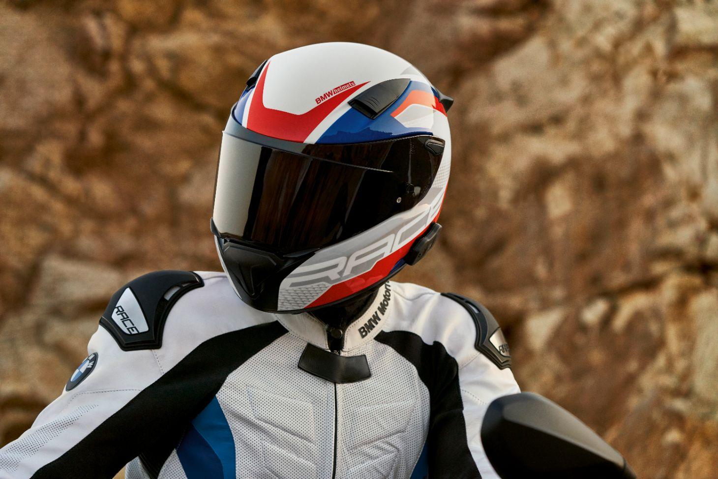 motociclista com capacete bmw motorrad branco com detalhes em vermelho e azul