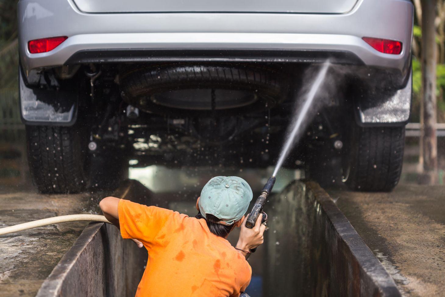 Trabalhador do lava jato pulverizando o chassi do carro
