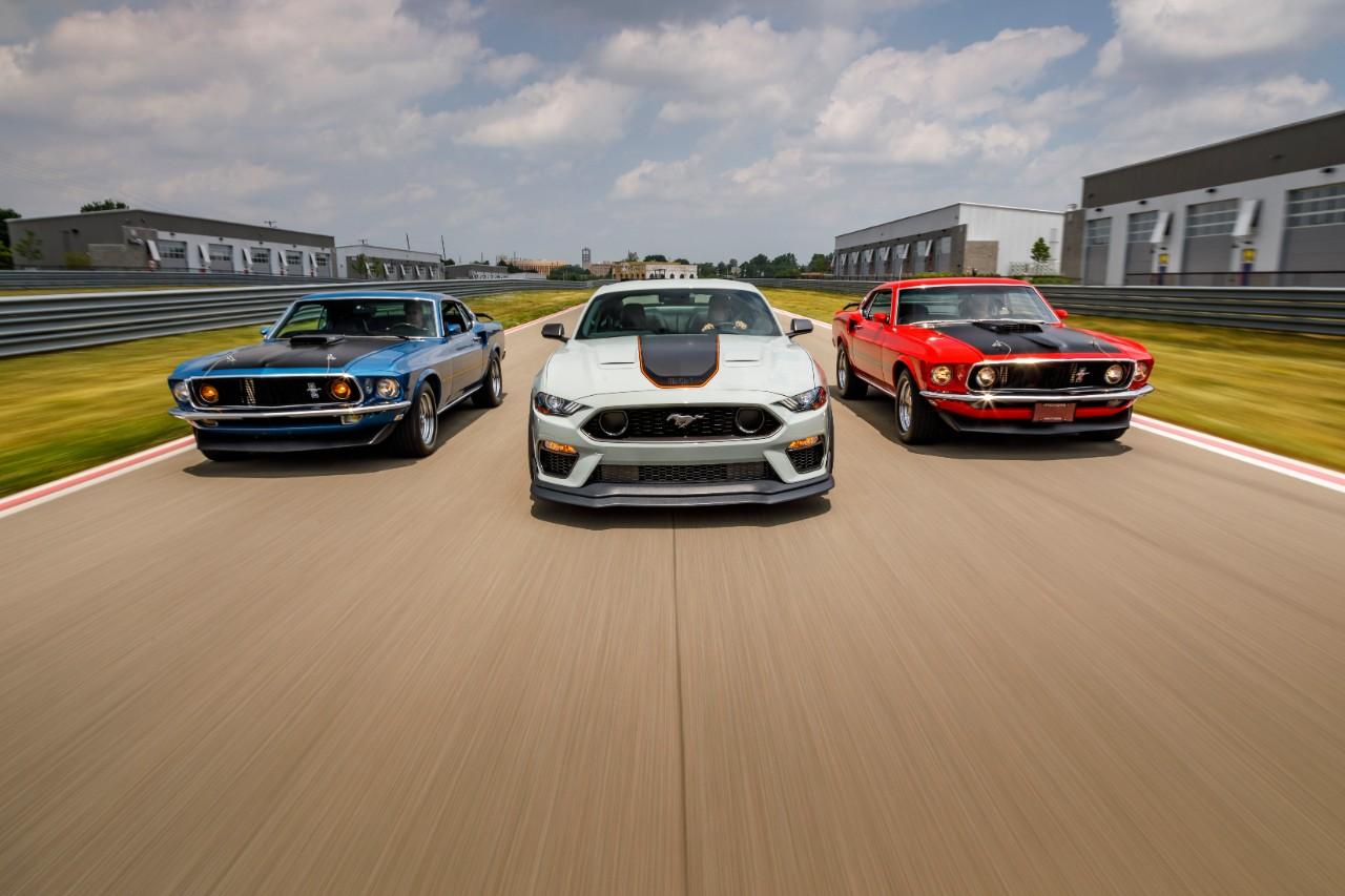 tres mustangs mach 1 2021 de geracoes diferentes em pista de corrida modelos azul branco e vermelho