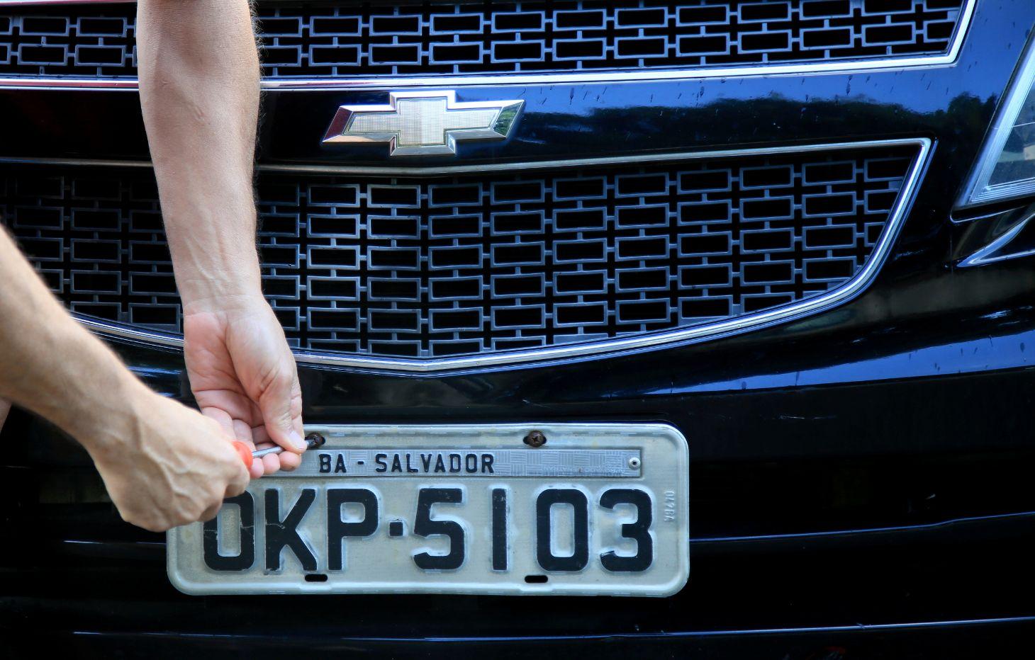homem instalando a placa de identificacao veicular piv cinza