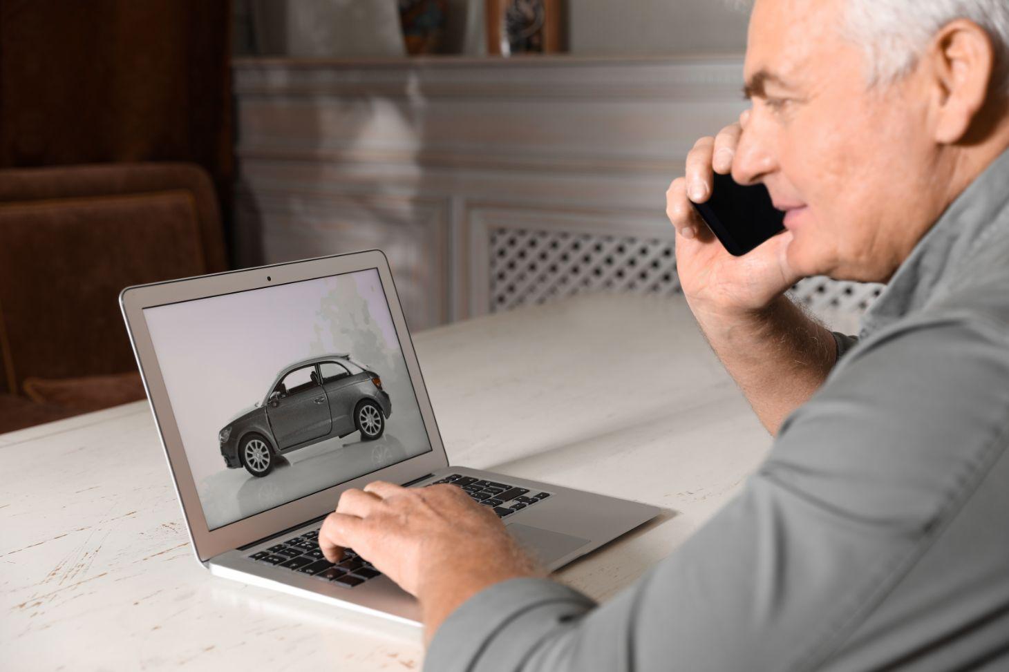 homem no telefone faz buscas no computador sobre veiculos