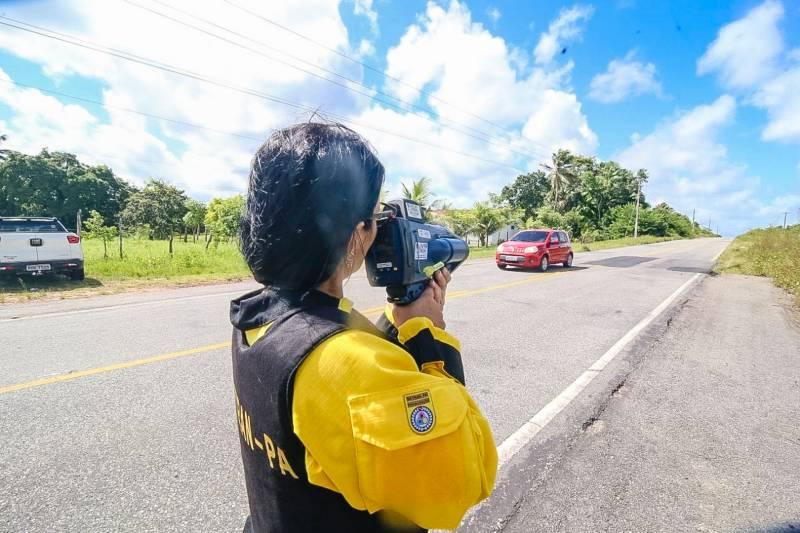 agente do detran com radar movel ou radar portatil em maos na beira de rodovia no para