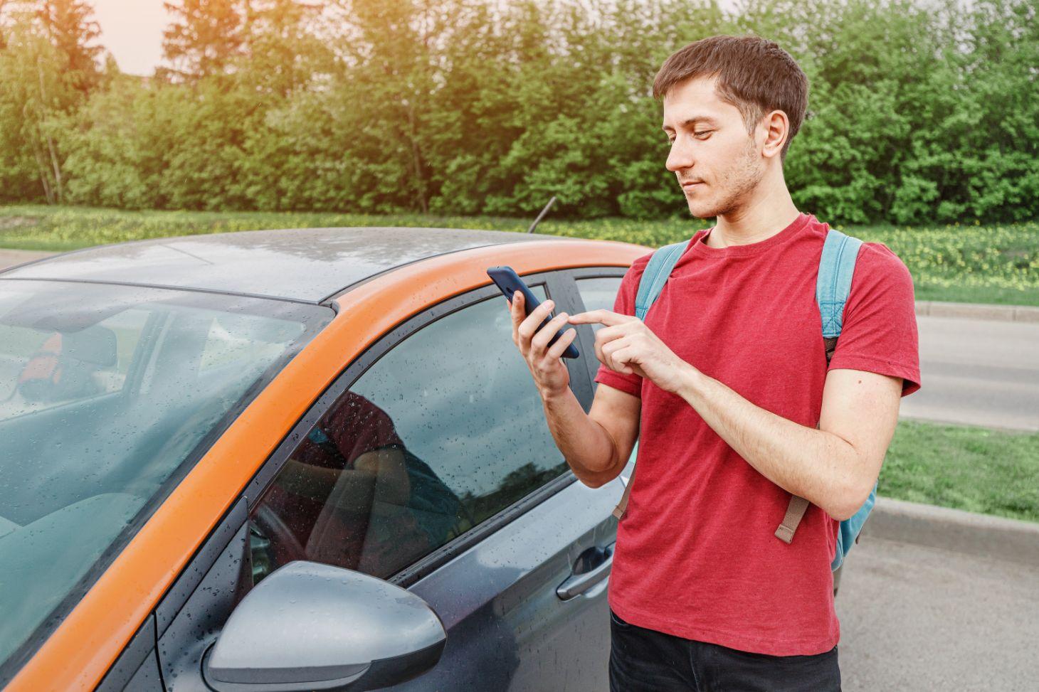 jovem com celular na mao com aplicativo de carsharing aberto representando carro multiplo