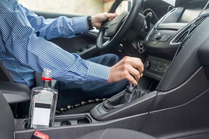 garrafa de bebida alcoolica aberta no porta objeto do carro com motorista dirigindo ao fundo