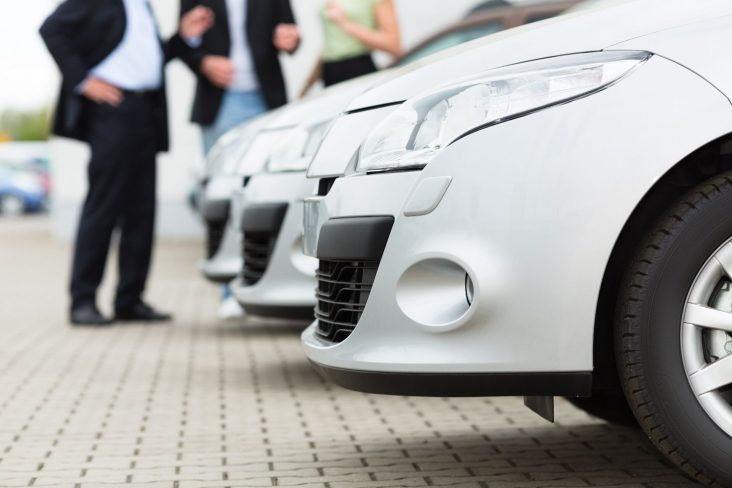 tres carros brancos em concessionaria com vendedor e compradores ao fundo