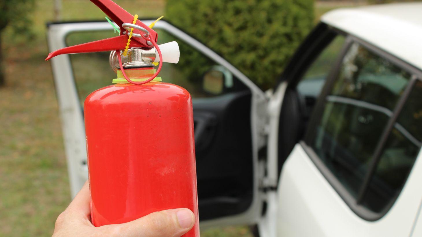 motorista segurando extintor incendio com carro automovel ao fundo