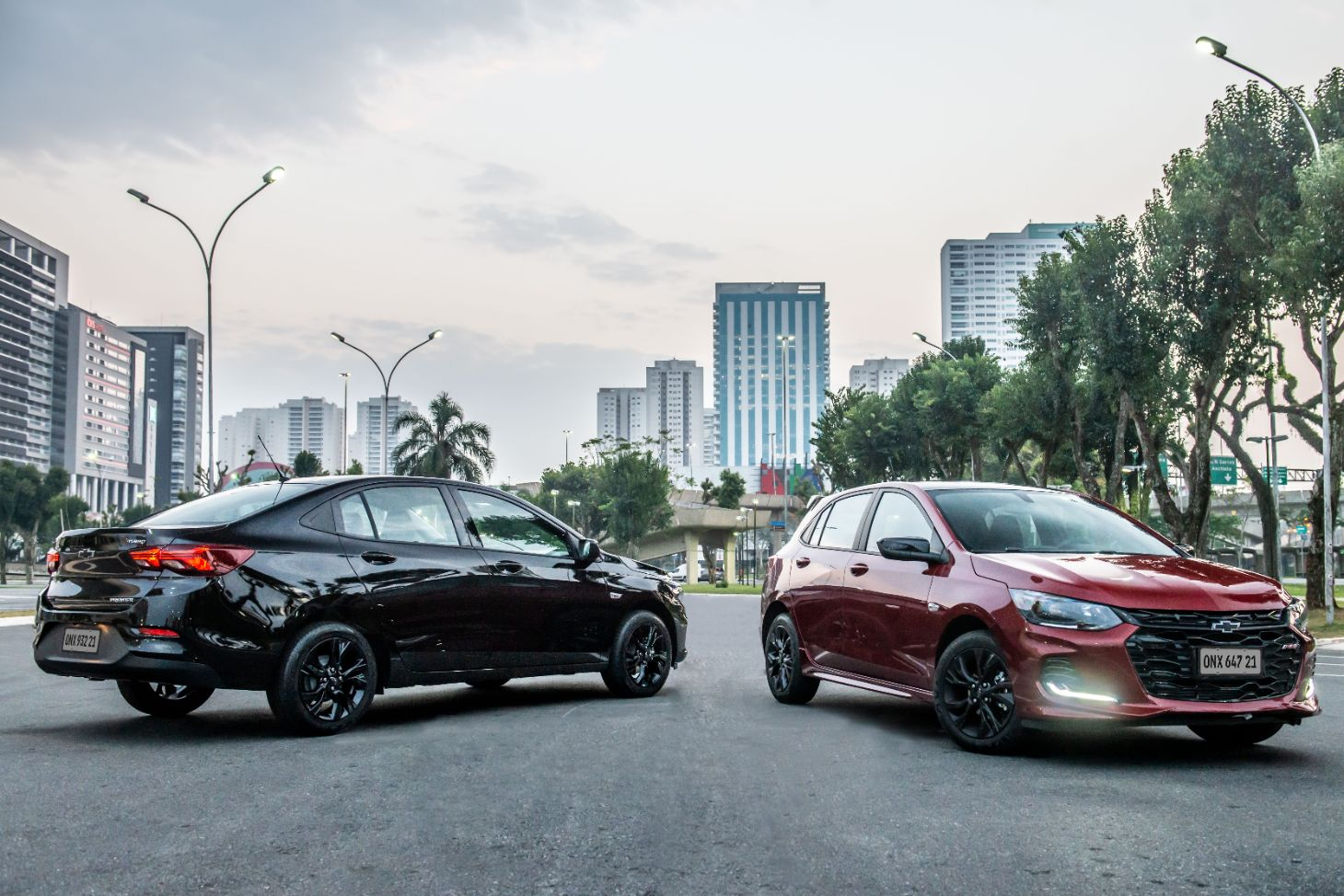 chevrolet onix plus midnight e onix rs vermelho estacionados