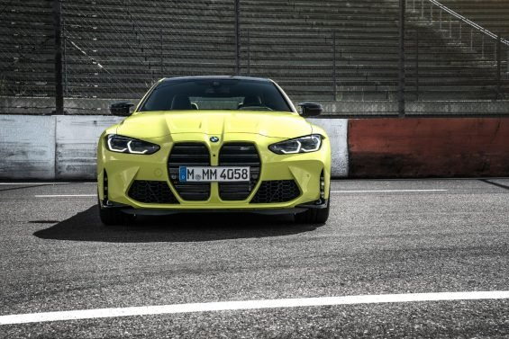 frente do bmw m4 coupe amarelo estacionado em pista